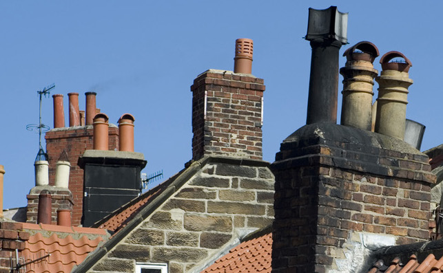 View of red tiled rooftops and a variety of different chimney pots in a typical English village